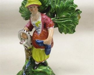 """A PRE-VICTORIAN STAFFORDSHIRE BOCAGE POTTERY FIGURE OF A WOMAN WITH A WATERING CAN. 5.5"""" TALL. CONDITION: chips on tips of leaves, multiple areas of missing paint flecks. c 1820. SIGNED 'WM'"""