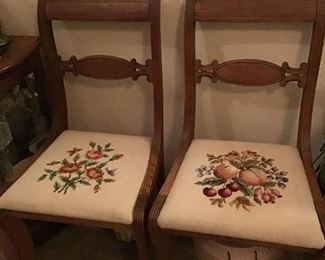 Pair of Mahogany chairs with needlepoint stitching on the cushions.