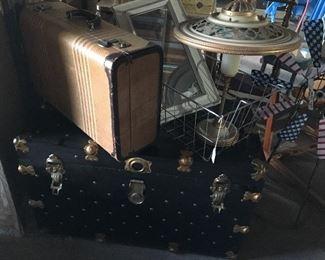 Trunk, suitcase, metal basket, light fixture.