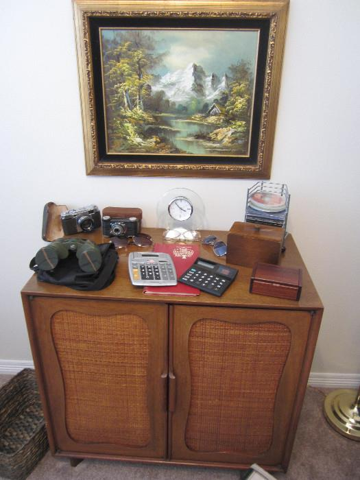 Nice cabinet, Vintage Argus and Yashica Cameras, McStar Binoculars, Vintage Royal Typewriter Excellent Condition.  Another G. Whitman painting