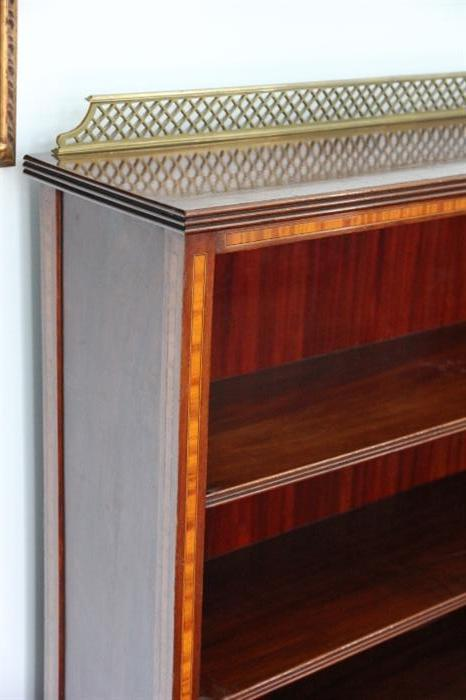detail of inlay and brass rail on bookcase