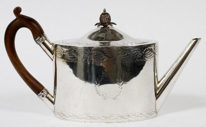 """Lot#1017, GEORGE III STERLING TEAPOT BY DUNCAN URQUHART & NAPHTALI HART, LONDON, 1799-1800, H 6"""", L 11""""An oval sterling silver teapot with chased borders and a laurel wreath at one side, having a hinged lid, pineapple finial, and wood scroll handle.  Hallmarks include a lion passant, crowned leopard, king's profile, and date letter D, as well as the maker's mark for Duncan Urquhart and Naphtali Hart (see additional photo).   Weighs approximately 14.5 troy oz."""