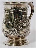 """Lot#1020, GEORGE III STERLING TANKARD, LONDON, 1772-73, H 5""""Repousse floral basket and scroll motifs, with a scroll handle.  Hallmarks include a lion passant, crowned leopard, date letter R, and partially rubbed maker's mark.  Weighs approximately 11.5 troy oz."""