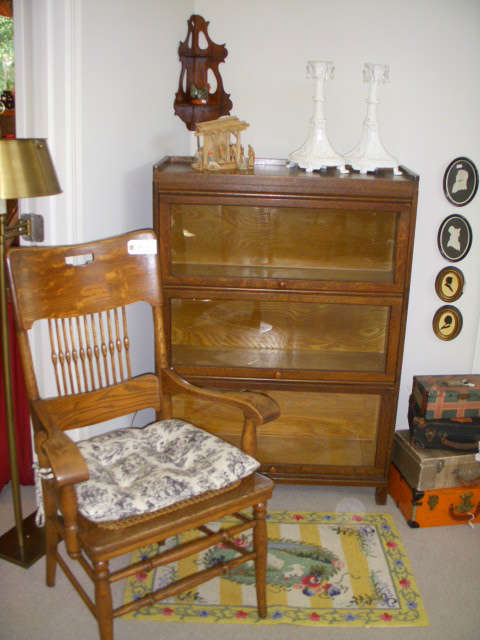 3 Section stack barristers bookcase, Oak arm chair with cane seat, Stack of small suitcases, Newer hooked-style rug
