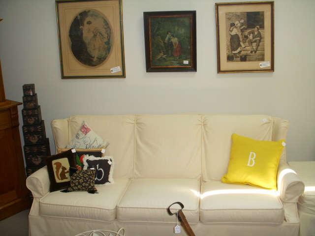 Vintage prints on wall.  Slip covered sofa (orange underneath!)