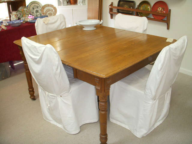 Oak dining table with center (fifth) leg for support.  Shown with 2 leaves in, and there are 4 more leaves (2 of those leaves are not original but fit nicely).  Chairs are rush seat ladderback chairs that have foam cushions and white slip covers added.  Covers can be removed.
