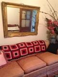 Vintage down-stuffed sofa and Hollywood Regency gold mirror. Second floor.