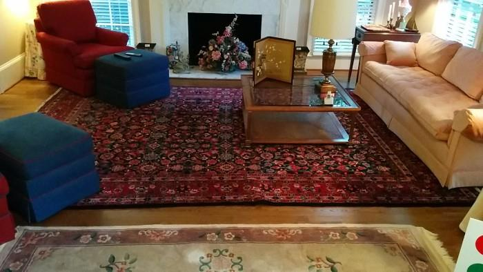 The living room is to the right of the front door, has a pair of red club chairs w/matching ottomans (contrast welts) another gorgeous Persian rug 8 ' x 10', glass/wood coffee table and a ttiity pink couch - no home should be without one! I think they purchased it from Graceland's estate sale...no peanut butter skid marks though.