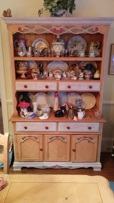"""Ahh, now here's something you don't see everyday. This is the hutch from a dining set that includes table w/leaf, six chairs and buffet, all tarted up in a """"French Country"""" style. The hutch is about to fall over with a mish-mash of smalls that must be seen to be believed."""