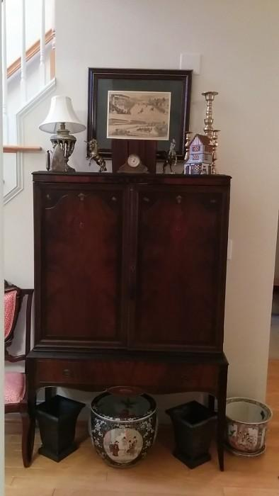 Vintage mahogany 2-door cabinet with assorted brass dust-catchers, obligatory seasonal light-up house, realistic unicorns (but no rainbows) vintage metal clock/bank, pair of metal planters.