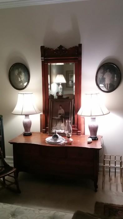"Antique dresser with Asian lamps, kerosene lanterns, old family photo and pair of old phots that look as if they were taken from the set of ""The Shining"""