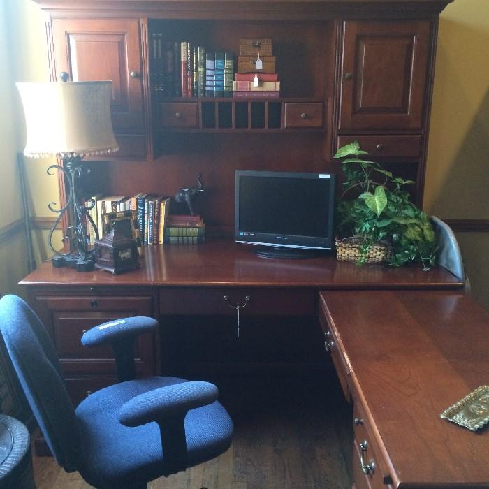 L-shaped desk unit; office chair; monitor; books; decorative items