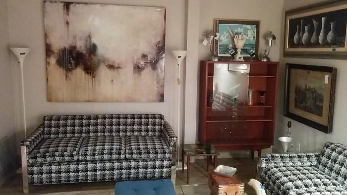 Impressive size, but not great wall art, pair of houndstooth sofas, pair of metal torchiere floor lamps, original artwork, Arne Vodder bookcase/display cabinet, pair of 1950's chrome table lamps (golfers).