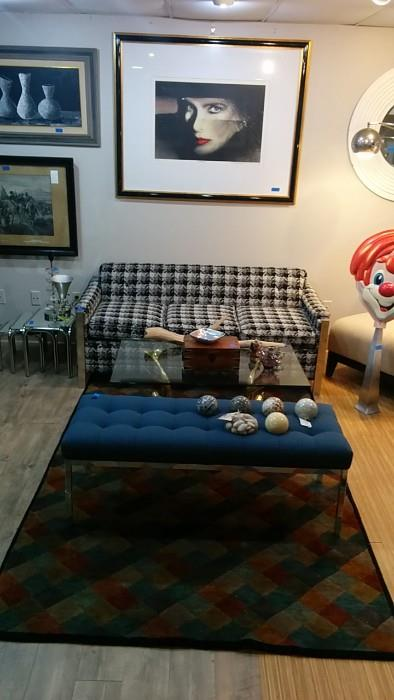 "Signed, numbered artwork by Paul Chelko, brass dolphin coffee table, chrome bench, w/blue cushion, 100% wool hand woven rug (8' 10"" x 5' 1"")."