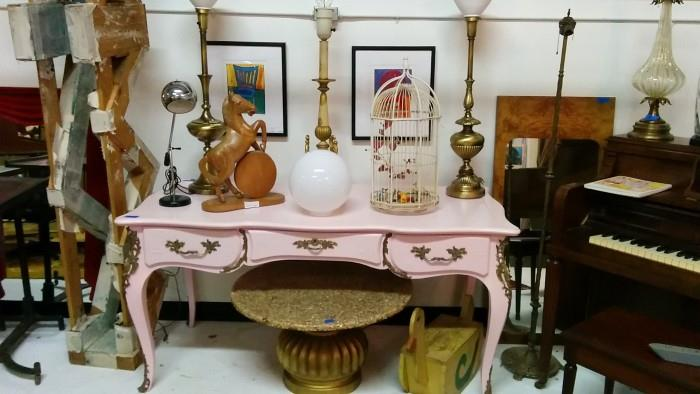 Wow - a visual feast (famine?) of overstimulation. Take one pink over-sprayed Chinoiserie desk, add hand-carved wooden horse, three brass table lamps, a black/chrome desk lamp, a birdcage and Grandpa's- homemade-woodworking-project-gone-wrong duck and you have a recipe for disaster!