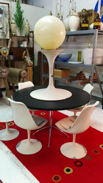 OK, this is a stretch, but I couldn't help myself. The Saarinen chairs are original, all need TLC. The legged chrome base looks the part, but the Saarinen table base has an added plastic globe for scale and visual foreplay. Did it work for you? Love the red rug. It reminds me that Valentine's is in the air, but so are dust mites. This rug is deemed mite-free by all governmental regulation agencies.