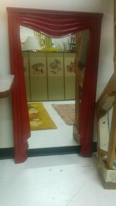 Umm, a red wooden mirror with carved curtain detailing, but why?