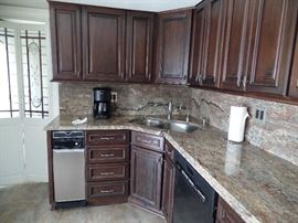 More cabinets and Granite counters, plus stainless steel sink and faucets-trash compactor