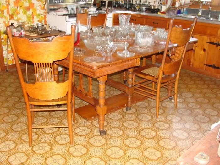Turn of the Century American Oak Dining Table with leaves and 3 matching chairs the base is beautifully carved and legs are supported by rare double wooden wheel casters. This piece is Gorgeous!