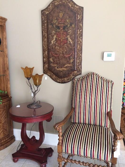 Barley twist striped upholstered armed chair; round top side table; stunning wall panel