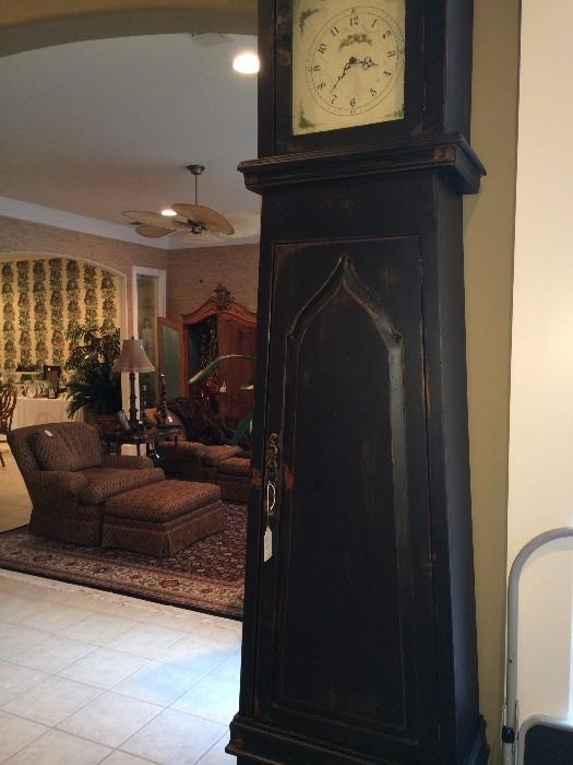 Extra tall decorative clock (not old); in background - two great club chairs with ottomans
