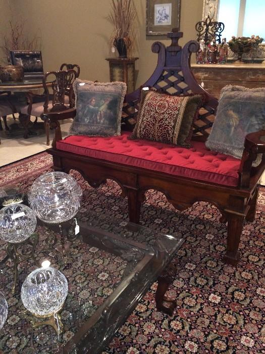 Ornate settee with red cushion; glass top coffee table