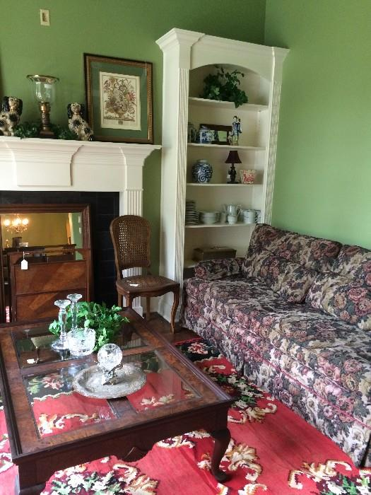 One of 5 sofas; glass top coffee table; cane chair; Staffordshire-style dogs; other decorative items; fabulous rug in greens/reds