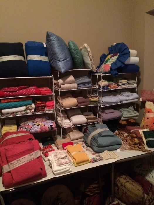 Many linens, pillows, and bedding