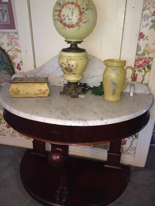 Antique demi-lune table with marble top; enamel box; Gone With the Wind lamp; satin glass pitcher;