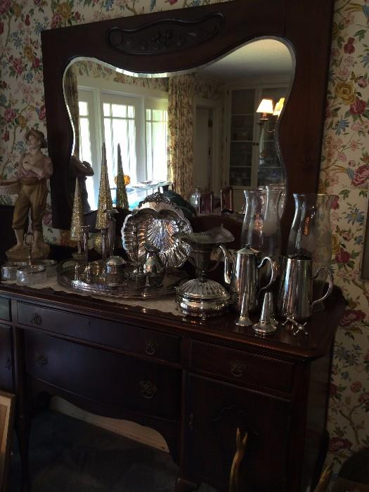 Antique buffet with beveled mirror; lots of silver plate serving pieces