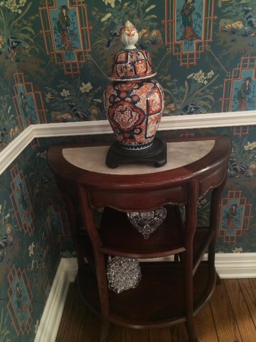One of two marble top demi-lune side tables; Imari ginger jar and crystal pieces