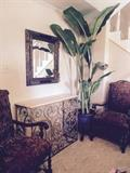very nice pair of vintage chairs, newly upholstered; gold washed iron credenza with stone surface, banana tree, nice planter on an iron tripod, and beveled mirror.