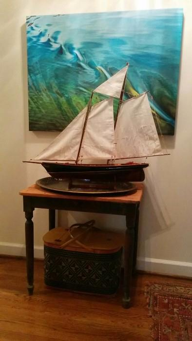 """An original Marilyn Suriani artwork, a ships model """"America"""", a perfect, chippy side table with heart pine top, a front drawer and Martian green legs."""