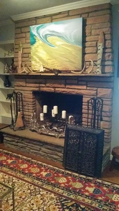 Another Marilyn Suriani original artwork above the stone mantel, deer antlers, wooden fish, two sets of fireplace tools, an antique cast iron door from a wood stove and an antique fire fender...