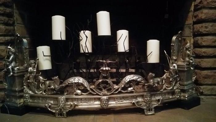Here's a close-up of the antique fire fender. It is nickle-plated, featuring amazing relief, with two, square black marble bases. there's a contemporary black candle holder rising from behind...