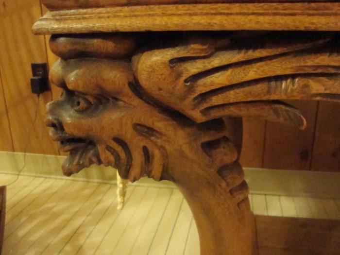 Carved head and wings on library table