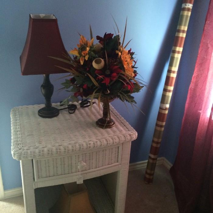 One of several white wicker side tables and floral arrangements