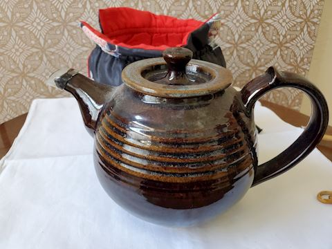 Brown earthenware teapot with cozy
