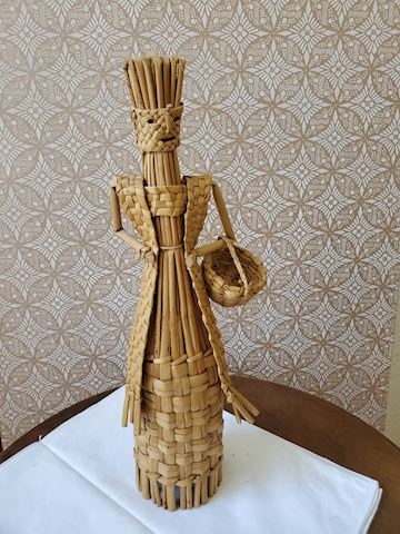 Woven read and straw woman figurine