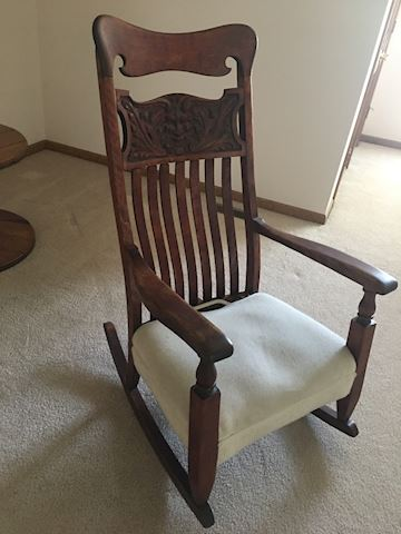 High back carved rocking chair with arms
