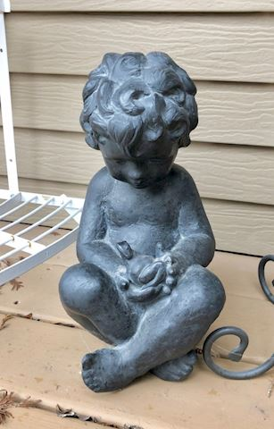 Small child with frog garden statue