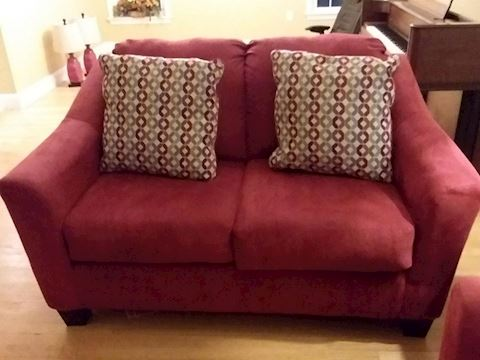 Red Upholstered Love Seat with Throw Pillows