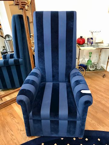 One high back upholstered chair in a blue tone