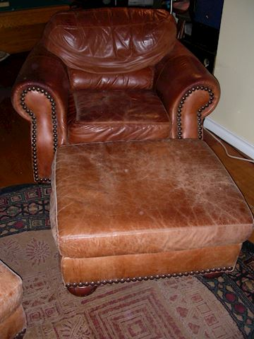 Pair of leather arm chairs and ottomans